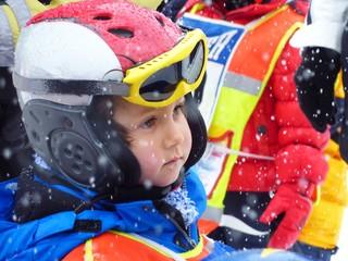 3-jähriger Junge ist konzentriert und angespannt vor dem Abschlussrennen seines Skikurses in der Kinderskischule in Tirol bei Schneetreiben
