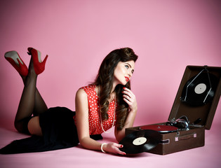 Glamorous pinup girl lying near retro gramophone holding LP vinyl record looking up on pink background