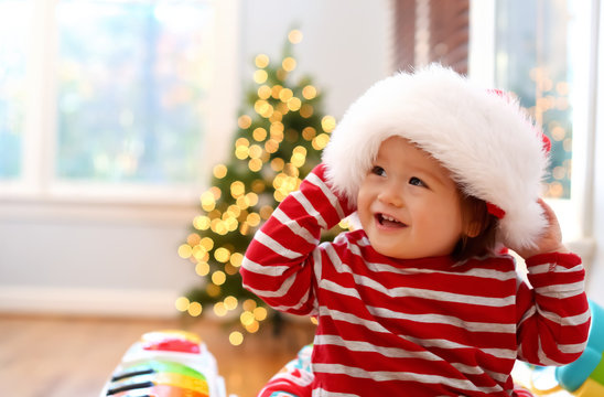 Happy toddler boy in a Santa hat playing on Christmas in his house