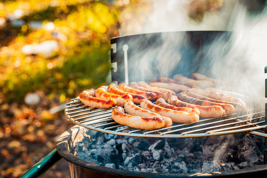 BBQ with fiery sausages on the grill outdoor picnic. Spending time together with the family at the grill. Social meetings, friends. Juicy and well-grilled sausages