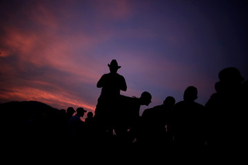 Migrants are silhouetted as a caravan from Central America en route to the United States make their way to San Pedro Tapanatepec from Arriaga