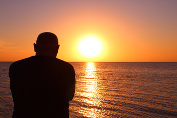 An elderly man sits by the sea and watches the sunset. Background. Landscape.