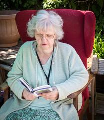 Grandma reading in the back garden, Southampton, UK