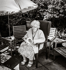 Black and White picture of grandma reading in the garden