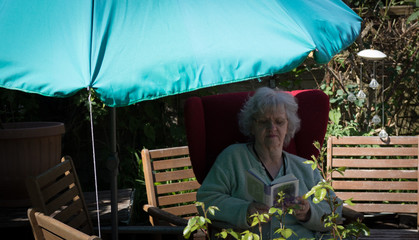 Grandma in the garden under the parasol
