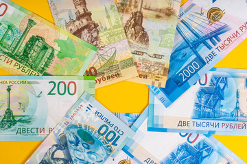Russian money. Bills laid out on the table. Banknotes on a yellow background. Finance.