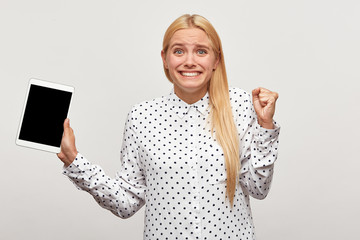 Blonde young woman clenched fist for joy, looks unbelievably gladden happy, with tablet in hand, black screen looks camera for your message or advertisement,mouth open,on white background