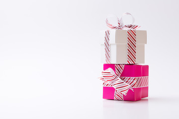 Pink and white color gift boxes tied with white red stripe ribbon isolated on white background