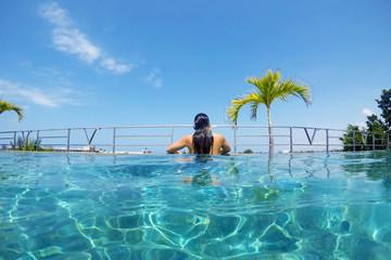 Girl in resort style infinity swimming pool overlooking Seminyak, Bali, Indonesia.
