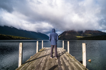 A man with blue jacket standing on dock enjoying with a view of lake Rotoiti, Nelsonlake National Park, New Zealand.