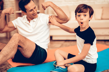 Man Sitting on Floor Showing Surprised Boy Muscles
