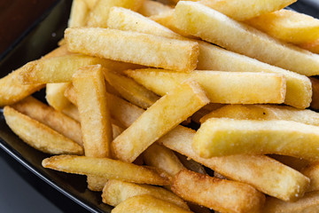French fries close-up in black plate with sauce.