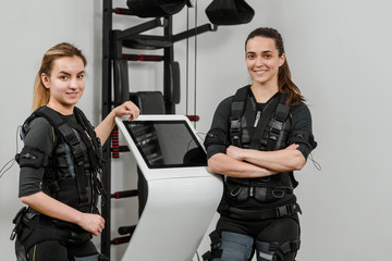 Happy smiling female athletes posing near EMS machine