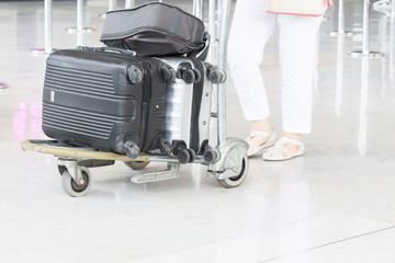 Woman walking suitcase luggage bag on trolley in the airport.