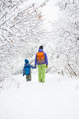Woman walks with her son over the snow-covered forest.