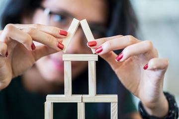 Woman arrange wooden blocks shaped a house