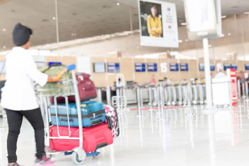 Woman walking suitcase luggage bag on trolley in the airport. Blurred motion selective