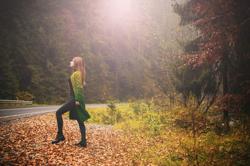 Travels concept. Woman with red hair rest in mountains and forest at cold time .Lady wear warm wool cardigan, nice fashionable casual clothes