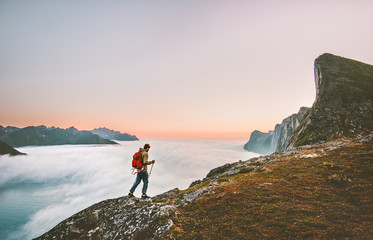 Man adventurer exploring sunset mountains hiking with backpack Traveling heathy lifestyle adventure concept active vacations outdoor voyage in Norway Wall mural