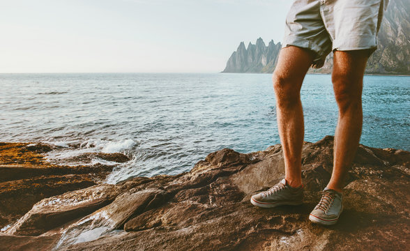 Feet man walking on sea beach outdoor Travel lifestyle fashion traveler wearing sneakers and shorts summer clothing