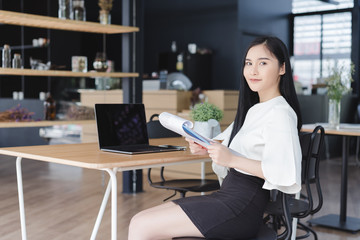 Smiling casual asian business woman in co working space or coffee shop.