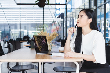 Happy asian business woman working with laptop in co working space or coffee shop.