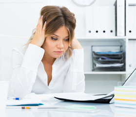 Pensive young girl in business clothes in modern office
