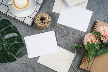 Two empty white greeting cards with flowers bouquet and envelope on concrete surface. Mockup template,top view,flat lay.