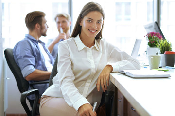 Designer in casual clothes is sitting, looking at camera and smiling, his colleagues are working in the background.