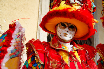 Colorful carnival red-yellow mask and costume at the traditional festival in Venice, Italy