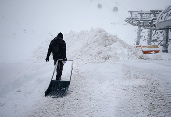 A man carries a shovel during snowfall after the Alpine Skiing World Cup Men's Giant Slalom race was canceled in Soelden