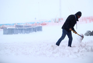 A man shovels snow in the finish area after the Alpine Skiing World Cup Men's Giant Slalom race was canceled in Soelden