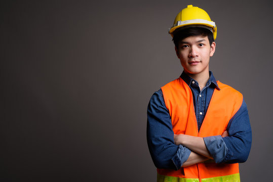 Young handsome Asian man construction worker against gray backgr