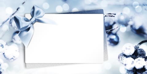 Fotomurales - gift or greeting card with blue ribbon bow on blurred blue christmas background, white copy space