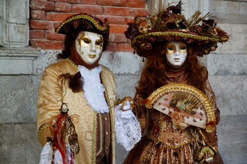 Colorful carnival gold-brown mask and costume at the traditional festival in Venice, Italy