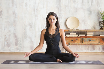 Young woman in a black tight suit meditates