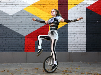 Girl clown rides a unicycle Wall mural
