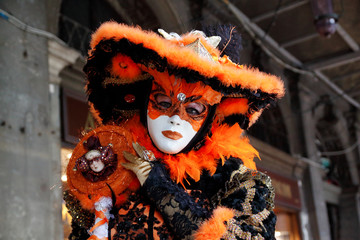 Colorful carnival black-orange-gold mask and costume at the traditional festival in Venice, Italy
