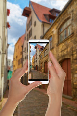 A tourist is taking a photo of european street with parked motor scooter in the old city in Riga on a mobile phone