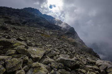 peak of Rysy mountain covered in mist. autumn ascent on hiking trails
