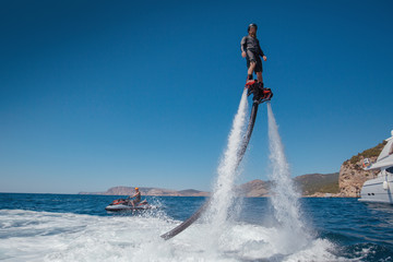Flyboarding and seariding on the Sea near the mountain island. Water summer extreme sports. Wall mural