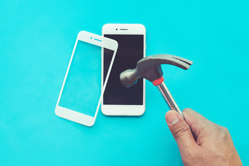 Male hand with hammer on tempered glass shield or film screen cover.Mobile phone protector concepts