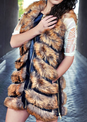 Fashion outdoor style portrait of young beautiful elegant woman in brown luxurious fur vest coat with black leather details with zipper walking on city street