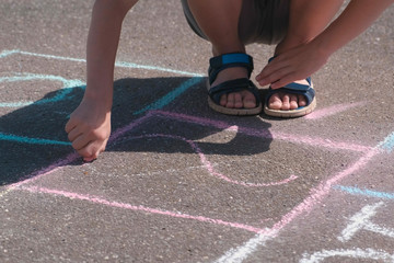 Boy is drawing hopscotch on the asphalt. Close-up hand and legs.