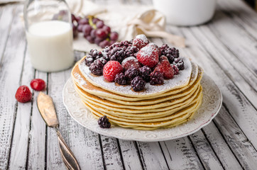 Homemade crepes with frozen berries, topped sugar