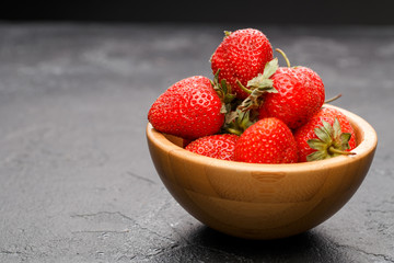 Photo close-up of ripe strawberry in wooden cup on black background