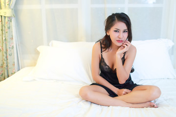 young asian woman with black see through dress toothache on bed