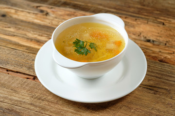 Broth - chicken soup with noodles in a white bowl