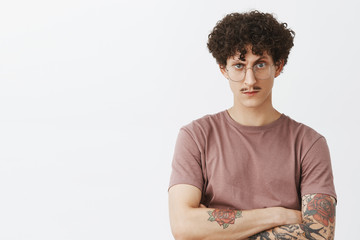 You cannot trick him. Portrait of intense suspicious and doubtful stylish modern hipster guy with fancy moustache tattooed arms and curly dark hair looking from under forehead doubtful in glasses