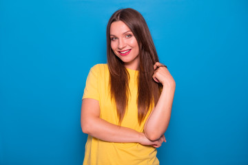 Cute brunette woman with long hair posing in yellow t-shirt on a blue background. Emotional portrait. She smiles happily with flawless white teeth and flirting